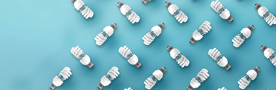 Viele Energiesparlampen vor türkisem Hintergrund